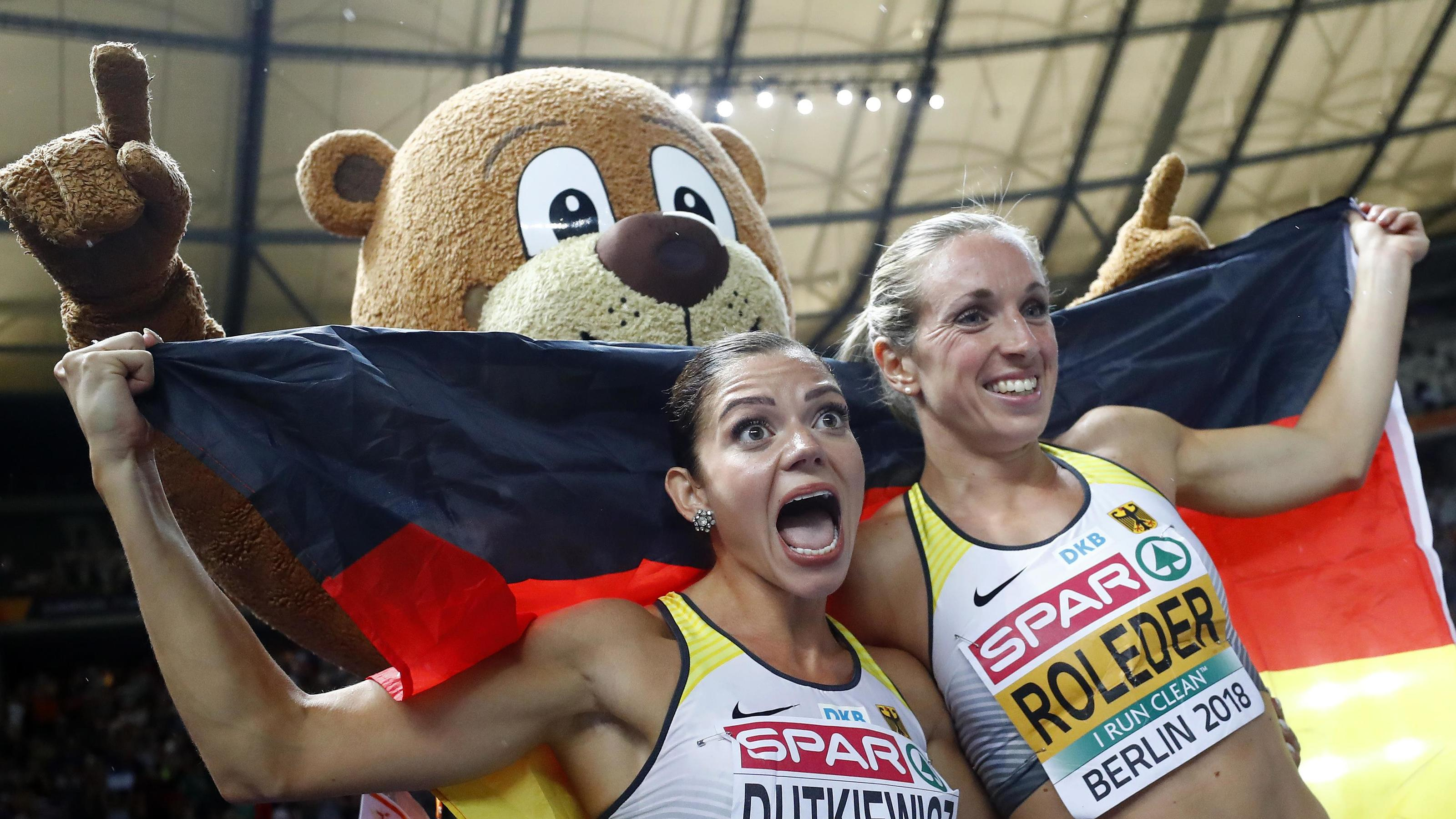 2018 European Championships - Women's 100m Hurdles Final - Olympic Stadium, Berlin, Germany - August 9, 2018 - Second placed Pamela Dutkiewicz of Germany and third placed Cindy Roleder of Germany celebrate with games mascot Berlino. REUTERS/Kai Pfaff