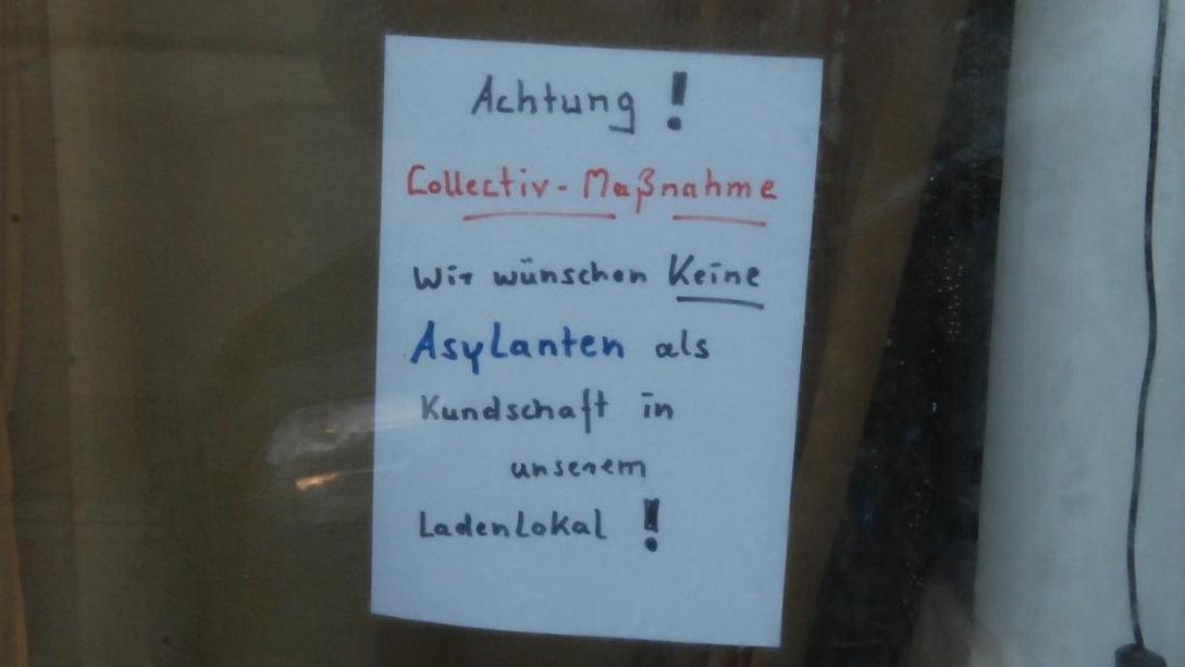 """Zettel an Esoterikladen in Töging mit der Aufschrift: """"""""Achtung! Collectiv-Maßnahme: Wir wünschen keine Asylanten als Kundschaft in unserem Ladenlokal!"""""""